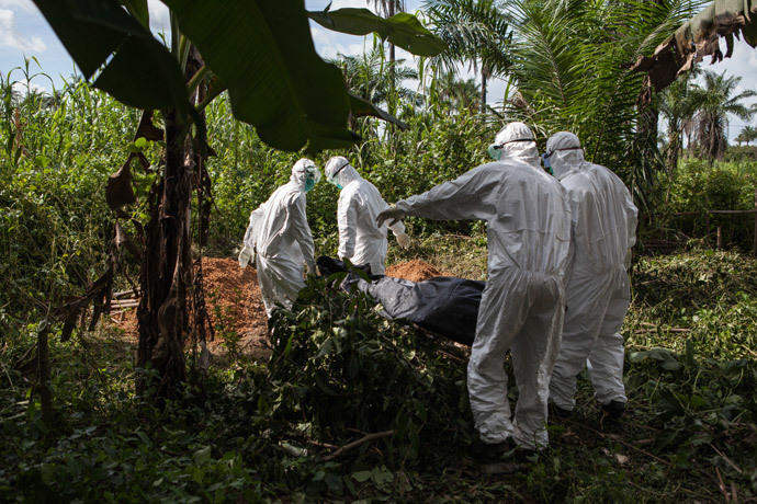 A specialized Ebola inhumation team carry the body of a recent Ebola victim to be buried, on October 6, 2014 in Magbonkoh. (AFP Photo / Florian Plaucheur)