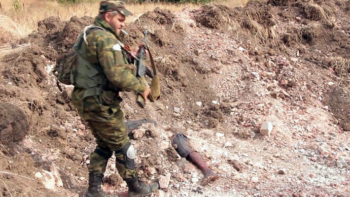 """A Donetsk People's Republic militiaman is at the site of the graves of peaceful residents discovered near Mine 22 """"Kommunar"""" outside Donetsk (still from video courtesy of the Ruptly international news agency.)"""
