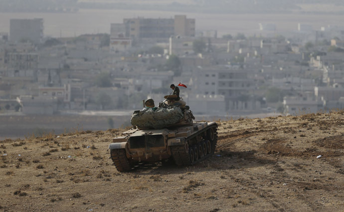 A Turkish soldier sits on top of a tank, with the Syrian town of Kobani in the background, as seen from the southeastern town of Suruc close to the Mursitpinar border crossing on the Turkish-Syrian border October 10, 2014. (Reuters/Umit Bektas)