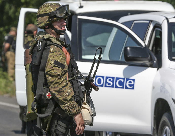 An armed pro-Russian separatist looks back next to a vehicle of the Organisation for Security and Cooperation in Europe's (OSCE) monitoring mission in Ukraine, on the way to the site in eastern Ukraine where the downed Malaysia Airlines flight MH17 crashed, outside Donetsk, July 30, 2014. (Reuters/Sergei Karpukhin)