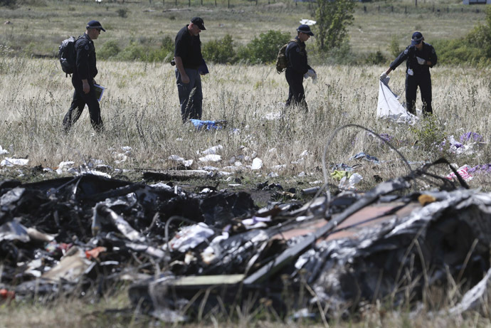 Members of a group of international experts inspect the territory at the site where the downed Malaysia Airlines flight MH17 crashed, near the village of Hrabove (Grabovo) in Donetsk region, eastern Ukraine August 1, 2014. (Reuters/Sergei Karpukhin)