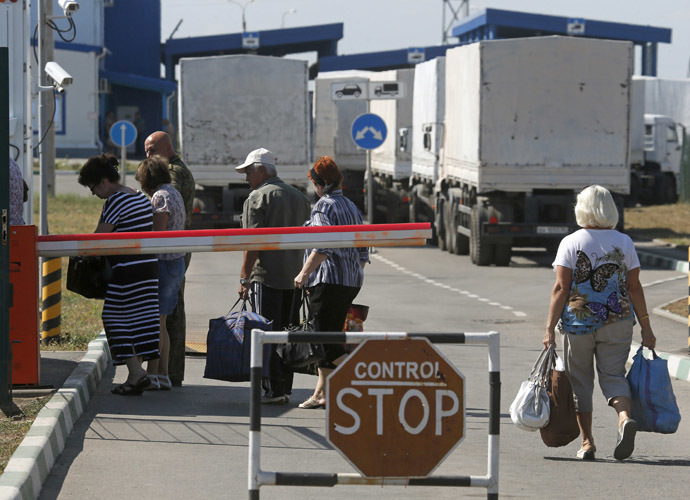 """Trucks of a Russian convoy carrying humanitarian aid for Ukraine are parked at a Russia-Ukraine border crossing point """"Donetsk"""", with people crossing the border in the foreground, in Rostov Region, August 21, 2014. (Reuters/Alexander Demianchuk)"""