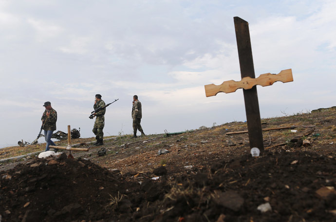 Militia members walk past an unmarked grave at Savur-Mohyla, a hill east of the city of Donetsk, August 28, 2014. (Reuters/Maxim Shemetov)