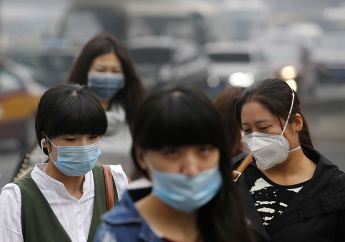 Pedestrians wearing masks walk on a street during a hazy day in Beijing October 10, 2014. (Reuters/Kim Kyung-Hoon)