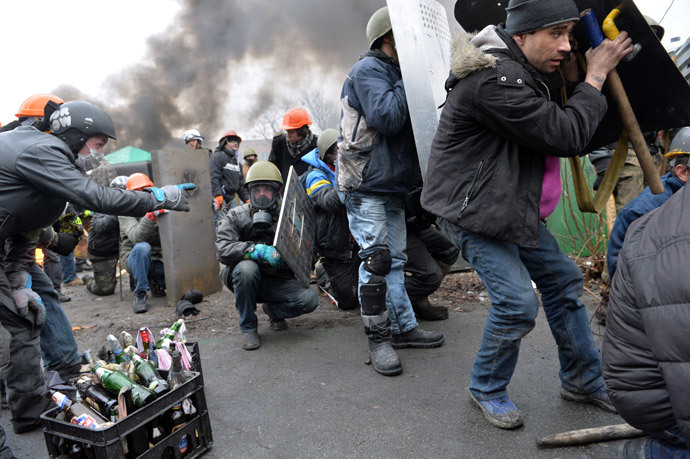Anti-government protesters take cover during clashes with riot police in central Kiev on February 20, 2014.(AFP Photo / Sergei Supinsky)
