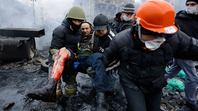 Anti-government protesters carry a man with a bullet wound on his leg during clashes with riot police in the Independence Square in Kiev February 20, 2014. (Reuters / Yannis Behrakis)