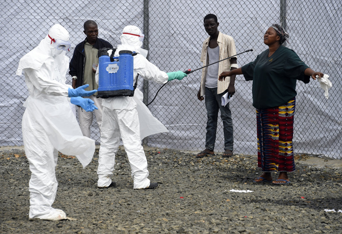 Medical personnel at the Ebola treatment centre at Island hospital in Monrovia (Liberia) disinfect people who had brought patients suspected of having the Ebola virus (AFP Photo / Pascal Guyot)