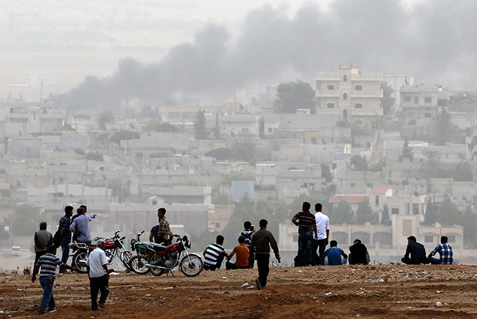 Turkish Kurds watch over the Syrian town of Kobani as they stand on top of a hill near Mursitpinar border crossing in the southeastern Turkish town of Suruc in Sanliurfa province October 11, 2014 (Reuters / Umit Bektas)