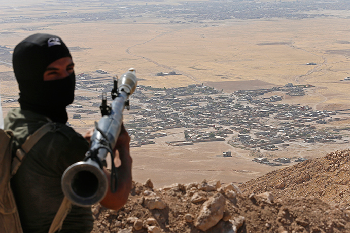 A Kurdish Peshmerga fighter holds a a rocket-propelled grenade launcher as he takes up position in an area overlooking Baretle village (background), which is controlled by the Islamic State, in Khazir, on the edge of Mosul September 8, 2014 (Reuters / Ahmed Jadallah)