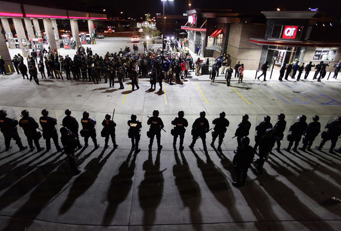 Police officers in riot gear hold a line as they watch demonstrators protest the shooting death of Michael Brown and 18-year-old Vonderrit Myers Jr. at a QuikTrip convince store and gas station October, 12 2014 in St. Louis, Missouri. (AFP Photo/Joshua Lott)