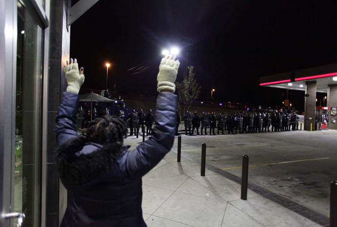 A demonstrator protesting the shooting death of Michael Brown and 18-year-old Vonderrit Myers Jr. holds her hands in the air as she looks at police officers in riot gear at a QuikTrip convince store and gas station October, 12 2014 in St. Louis, Missouri. (AFP Photo/Joshua Lott)
