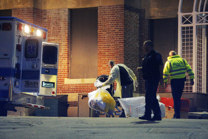 A man collects and bags items behind the ambulance used to transport a patient with possible Ebola symptoms to Beth Israel Deaconess Medical Center in Boston, Massachusetts October 12, 2014. (Reuters/Brian Snyder)