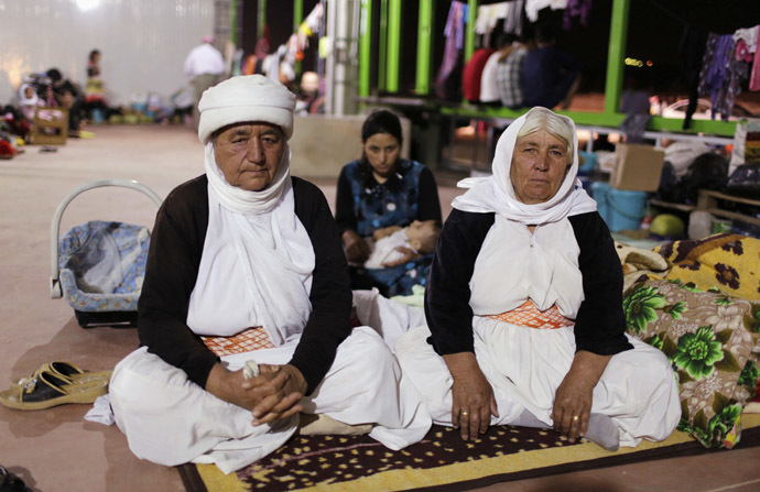 Women from the minority Yazidi sect, who fled violence in the Iraqi town of Sinjar, sit on the ground in an abandoned warehouse in Dohuk province August 22, 2014. (Reuters/Youssef Boudlal)