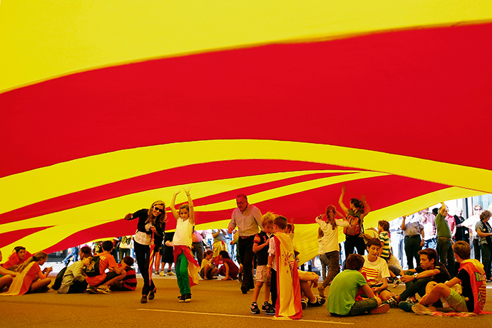 Spanish unionists demonstrators sit under a giant Catalonian flag during a rally at Catalonia square on Spain's National Day in Barcelona October 12, 2014 (Reuters / Albert Gea)