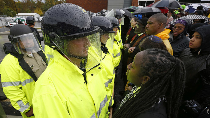 Protestors stand in front of the riot police during a protest at the Ferguson Police Department in Ferguson, Missouri, October 13, 2014. (Reuters/Jim Young)