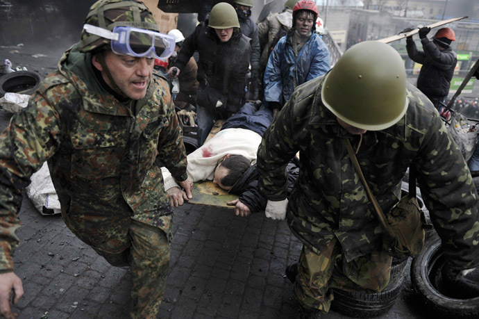 Protesters carry a wounded protester during clashes with polie, after gaining new positions near the Independence square in Kiev on February 20, 2014.(AFP Photo/Louisa Gouliamaki)