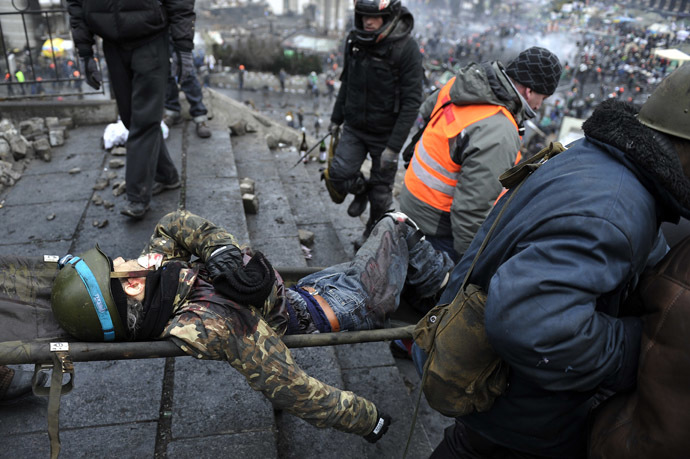 Protesters evacuate a wounded demonstrator from Independence square, dubbed Maidan, in Kiev on February 20, 2014. (AFP Photo/Louisa Gouliamaki)