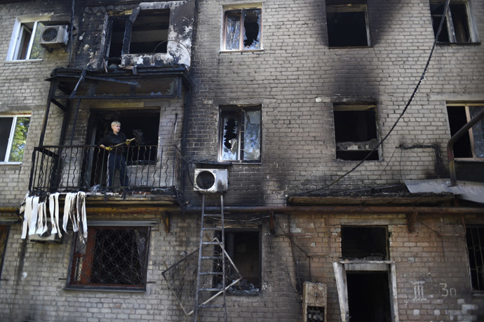 A man cleans up his burnt flat after a building was hit by shelling this morning in the Kievsky district near the international airport on September 17, 2014 in Donetsk, eastern Ukraine. (AFP Photo/Philippe Desmazes)