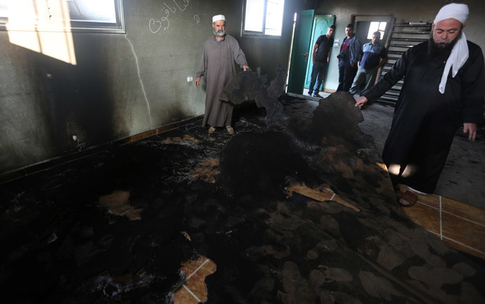 Palestinian Muslim clerics inspect the inside of a mosque allegedly burnt by Jewish settlers, in the village of Aqraba, in the Israeli occupied Palestinian West Bank, near the northen city of Nablus, on October 14, 2014. (AFP Photo / Jaafar Ashtiyeh)