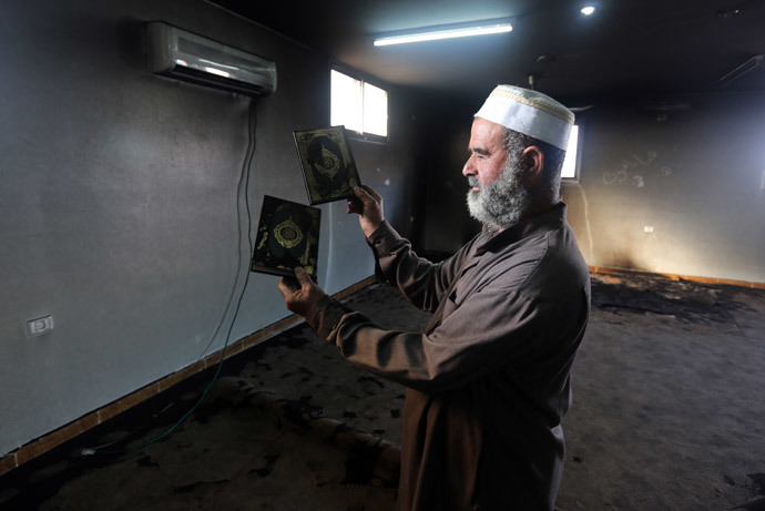 A Palestinian Muslim cleric holds up a burnt copy of the Koran, Islams holy book, in a mosque allegedly burnt by Jewish settlers, in the village of Aqraba, in the Israeli occupied Palestinian West Bank, near the northen city of Nablus, on October 14, 2014. (AFP Photo / Jaafar Ashtiyeh)