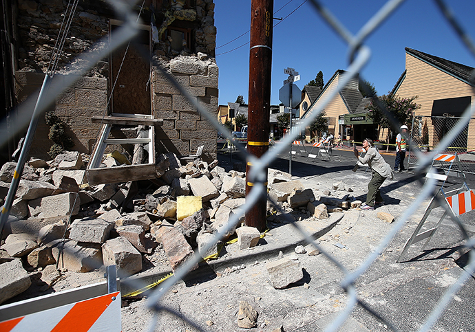 A passerby stops to take a picture of the earthquake-damaged Vintner's Collective building on August 26, 2014 in Napa, California. (Justin Sullivan / Getty Images / AFP)