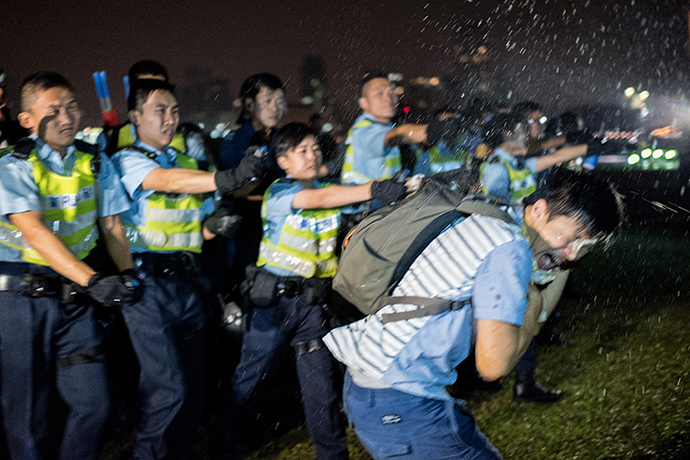 Police officers spray a protester in the face with pepper spray in Hong Kong on October 15, 2014. (AFP Photo / Alex Ogle)