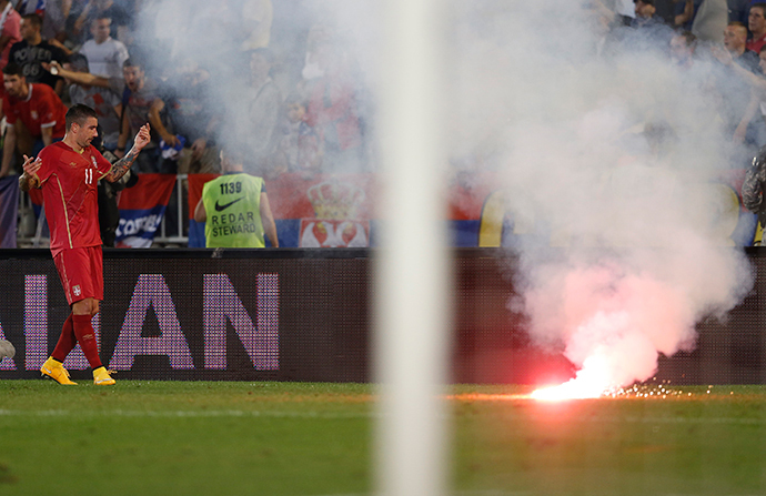 Aleksandar Kolarov of Serbia reacts as flares are thrown to the pitch during their Euro 2016 Group I qualifying soccer match against Albania at the FK Partizan stadium in Belgrade October 14, 2014. (Reuters / Marko Djurica)