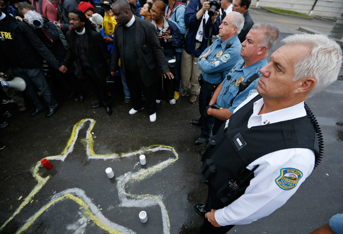 Police officers stand over a chalk outline of a body during a protest at the Ferguson Police Department in Ferguson, Missouri.(Reuters / Jim Young)