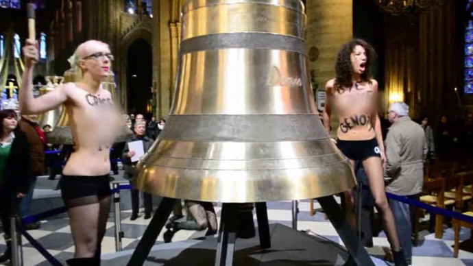 "Femen strike bells and shout ""Pope no more!"" and ""Clear off, homophobe!"". February, 2013. (Screenshot from RT report)"