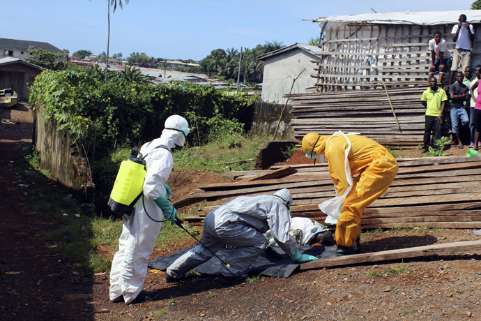 Health workers remove the body a woman who died from the Ebola virus in the Aberdeen district of Freetown, Sierra Leone, October 14, 2014. (Reuters/Josephus Olu-Mammah)