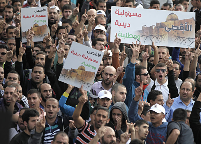 Palestinians shout slogans holding placards as they gather near the entrance of al-Aqsa mosque compound to protest after authorities restricted access to the esplanade on October 15, 2014 outside Jerusalem's Old City. (AFP Photo/Ahmad Gharabli)