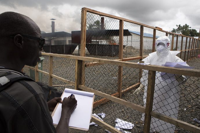 A health worker (R) wearing protective equipment provides his colleague with patient data at the end of his shift from the Ebola treatment centre at the Island Clinic in Monrovia, September 30, 2014. (Reuters/Christopher Black)
