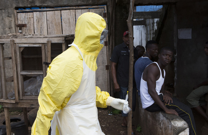 A health worker in protective equipment carries a sample taken from the body of someone who is suspected to have died from Ebola virus, near Rokupa Hospital, Freetown October 6, 2014. (Reuters/Christopher Black)
