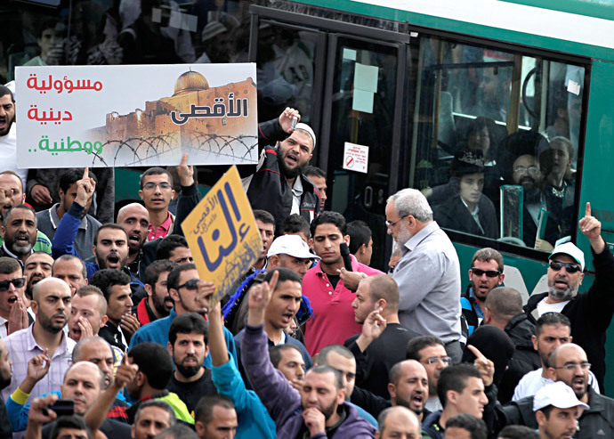 Palestinians shout slogans while Orthodox Jews look at the scene from a bus passing by, during a rally near the entrance of al-Aqsa mosque compound to protest after authorities restricted access to the esplanade on October 15, 2014 outside Jerusalem's Old City. (AFP Photo / Ahmad Gharabli)