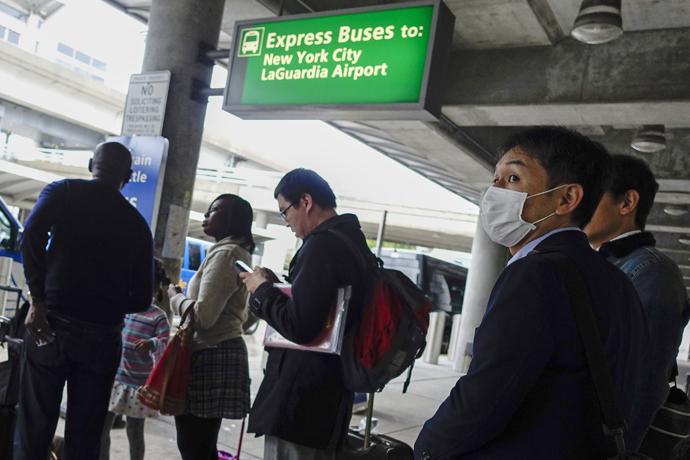 A passenger wears a mask as he exits JFK International Airport in New York. (Reuters/Eduardo Munoz)