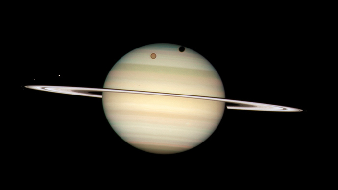 An image of four moons of Saturn passing in front of their parent planet in seen this image taken by NASA's Hubble Space Telescope (Reuters / NASA)