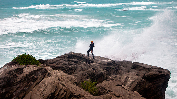 A man takes photos while standing on a cliff on the island's south shore battered by winds from approaching Hurricane Gonzalo, in Astwood Park, October 17, 2014 (Reuters / Nicola Muirhead)