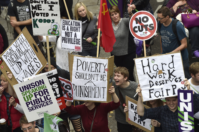 Protestors hold placards as they march through central London, October 18, 2014. (Reuters / Toby Melville)