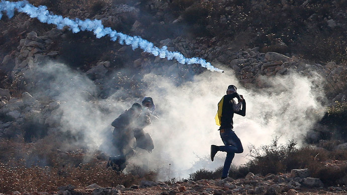 Palestinian protesters run from tear gas fired by Israeli troops during clashes at a protest to show solidarity with al-Aqsa mosque, outside Israel's Ofer military prison near the West Bank city of Ramallah October 17, 2014.(Reuters / Ammar Awad)