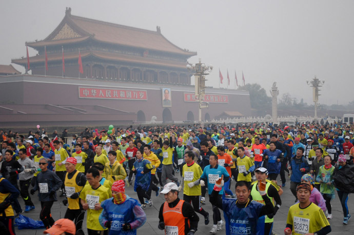 Runners take part in the 34th Beijing International Marathon which began at Tiananmen Square in Beijing on October 19, 2014, with many of the tens of thousands of participants wearing face masks, as the 42-kilometer course ended at the Olympic Park. (AFP Photo/China Out)