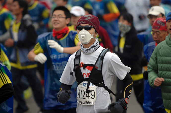 A runner wears a mask as he takes part in the 34th Beijing International Marathon which began at Tiananmen Square in Beijing on October 19, 2014. (AFP Photo/China Out)