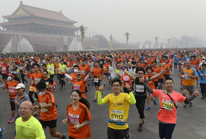 Participants run past the Tiananmen gate with a portrait of China's late leader Mao Zedong on a hazy day during the Beijing International Marathon in Beijing October 19, 2014. (Reuters/Stringer)