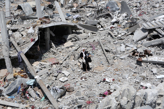 A Palestinian woman walks on the rubble of destroyed houses carrying items she collected in hers on September 13, 2014 in Khan Yunis' Khuzaa neighbourhood in the southern Gaza Strip, an area which was devastated after the Israeli bombing during the summer's fierce offensive on the Gaza Strip. (AFP Photo / Said Khatib)