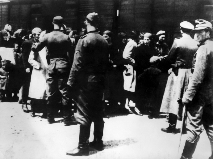 German soldiers, members of SS units, lead a new transport of prisoners to the gas chambers at the Oswiecim (Auschwitz) concentration camp. (AFP Pрщещ)