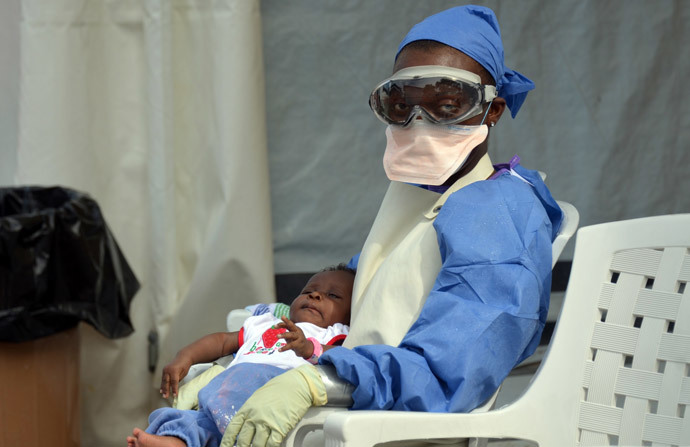 A Liberian health worker holds a baby infected with the Ebola virus at the NGO Medecins Sans Frontieres (Doctors Without Borders) Ebola treatment center in Monrovia. (AFP Photo / Zoom Dosso)