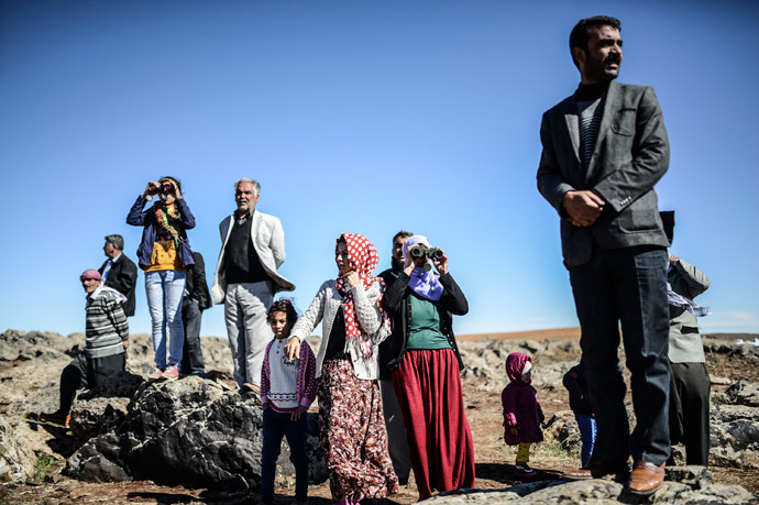 Members of the Syrian Kurdish Altay family try to spot on October 20, 2014 from the Turkish Syrian border village of Mursitpinar, their relative, Zamani Suruc, who is fighting Islamic State (IS) jihadists in the Syrian border town of Kobane, also known as Ain al-Arab. (AFP Photo / Bulent Kilic)