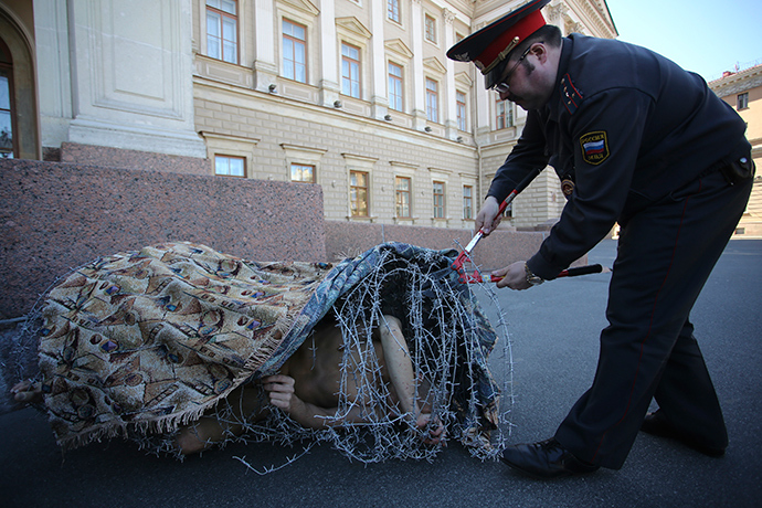 Artist Pyotr Pavlensky lies on the ground, wrapped in barbed wire roll, during a protest action in St. Petersburg May 3, 2013 (Reuters / Artur Bainozarov)