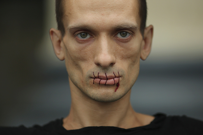 "Artist Pyotr Pavlensky, a supporter of jailed members of female punk band ""Pussy Riot"", looks on with his mouth sewed up as he protests outside the Kazan Cathedral in St. Petersburg (REUTERS / Trend Photo Agency / Handout)"
