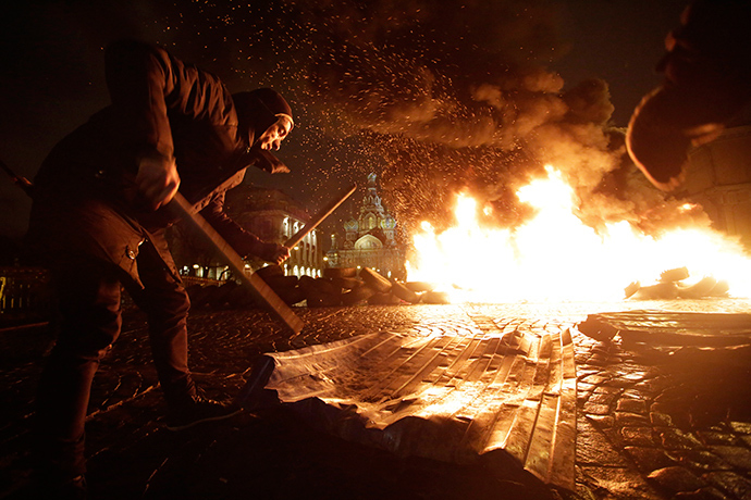 "Artist Pyotr Pavlensky drums with sticks as tyres burn during a performance called ""Freedom"", in support of Ukrainian anti-government protesters who held rallies in Maidan Nezalezhnosti or Independence Square in Kiev, in front of the Church of the Saviour on Spilled Blood in central St. Petersburg February 23, 2014 (Reuters / Maxim Zmeyev)"