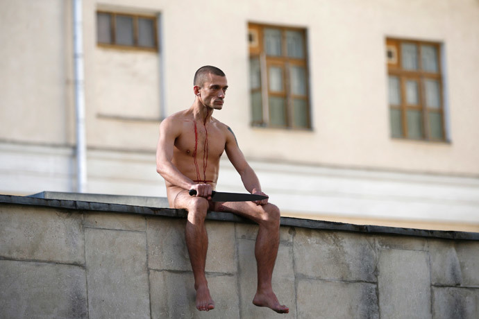 "Artist Pyotr Pavlensky sits on the wall enclosing the Serbsky State Scientific Center for Social and Forensic Psychiatry after he cut off a part of his earlobe during his protest action titled ""Segregation"" in Moscow October 19, 2014. (Reuters / Maxim Zmeyev)"